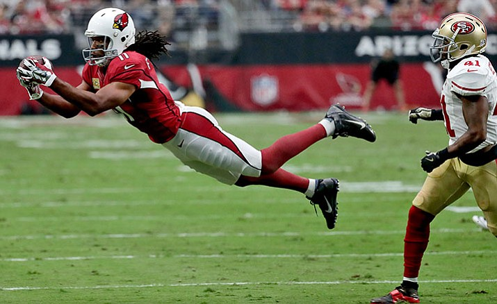 Arizona Cardinals wide receiver Larry Fitzgerald (11) makes a diving catch as San Francisco 49ers strong safety Antoine Bethea (41) defends during the first half of an NFL football game, Sunday, Nov. 13, in Glendale, Ariz.