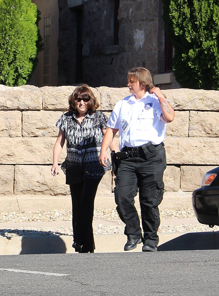 Diane Maxine Richards, accused in the largest embezzlement in Kingman history, walks closely behind a security guard employed by Mohave County Superior Court on Monday after a brief court appearance.