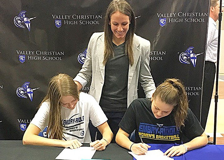 Embry-Riddle women's basketball coach Rebecca Burke stands over Megan Timmer, left, and Bethany Wolph, as they sign to play for the Eagles during the 2017-2018 season. Timmer and Wolph play for Chandler-based Valley Christian and led the Trojans to a 31-3 overall record and Division III state finals appearance in 2015-2016. (Courtesy/ERAU Athletics)