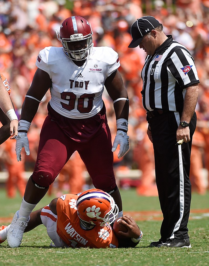 Troy defensive tackle Trevon Sanders (90) stands over Clemson quarterback Deshaun Watson (4) after a play during the first half of an NCAA college football game Sept. 10, in Clemson, S.C. The newly ranked Troy Trojans play Arkansas State on Thursday.