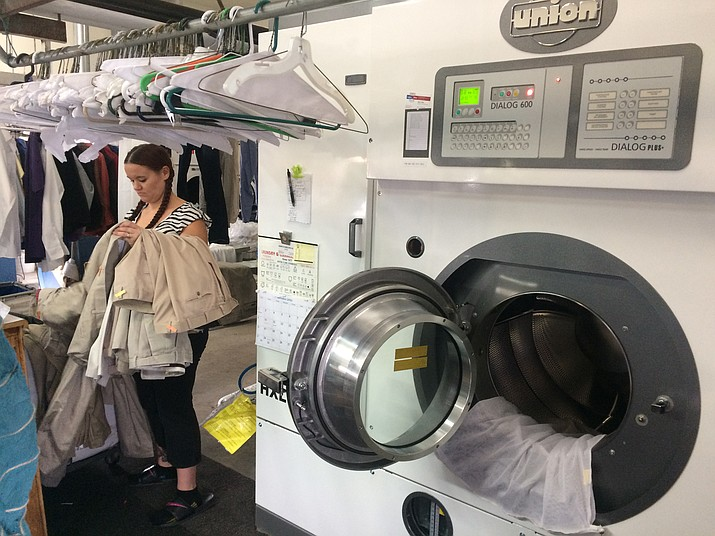 Tina Wolf, manager at Toni's Cleaners, sorts clothes before placing them in the new Union 800 Series dry cleaning machine that meets EPA standards for the Clean Air Act. New owner Sunil Patel invested $45,000 in the machine.