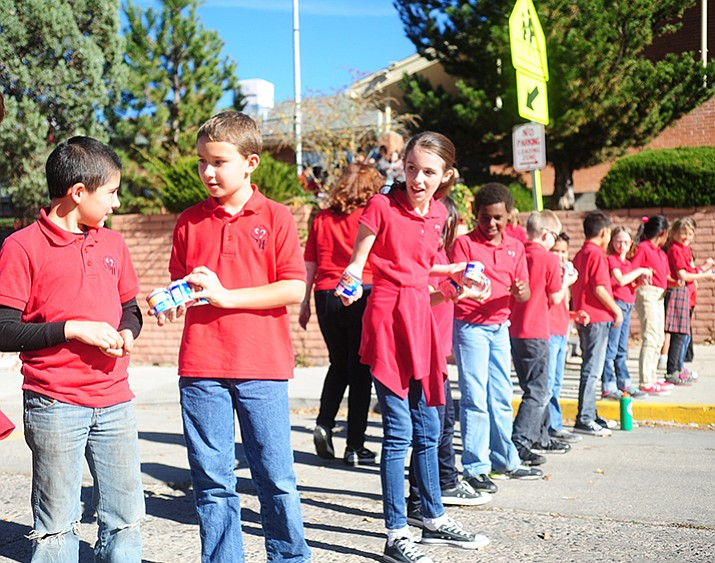 Students from the Sacred Heart School in Prescott create a human food chain to pass the canned goods across the street following their annual canned food drive on November 19, 2016. (Les Stukenberg/Courier)