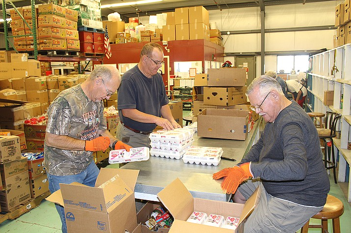 Volunteers Vern Tillberg, left, Dennis Anker and Troy Dobbs examine and pack eggs Thursday at the Kingman Area Food Bank.