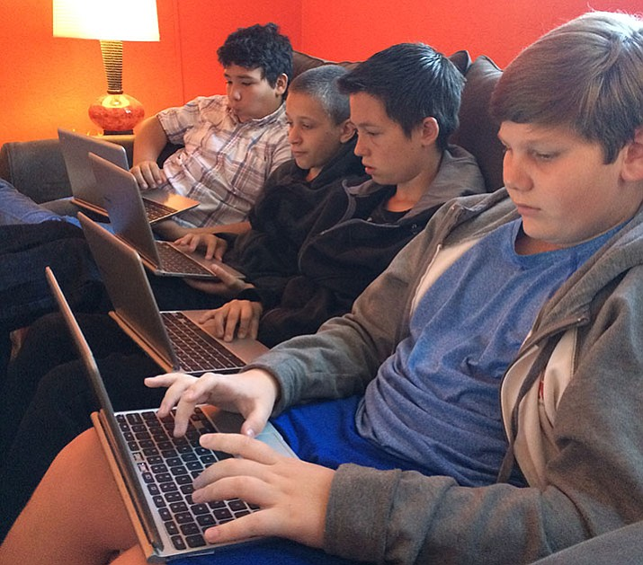 Four seventh-grade boys work on an essay in Wendy Tollefsen's experimental classroom.