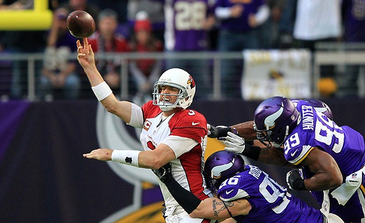 Arizona Cardinals quarterback Carson Palmer passes while getting pressured by Minnesota Vikings defenders Brian Robison (96) and Danielle Hunter (99) during the second half of an NFL football game Sunday, Nov. 20, in Minneapolis.