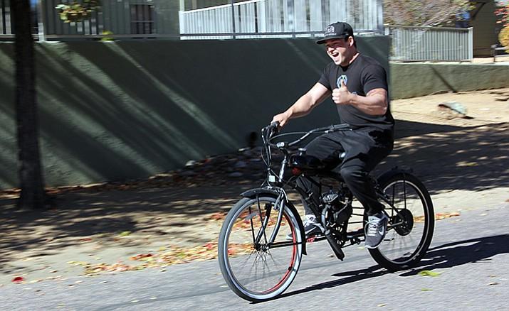 Dakota Schatz rides his motorized bicycle down the Prescott street he lives on.