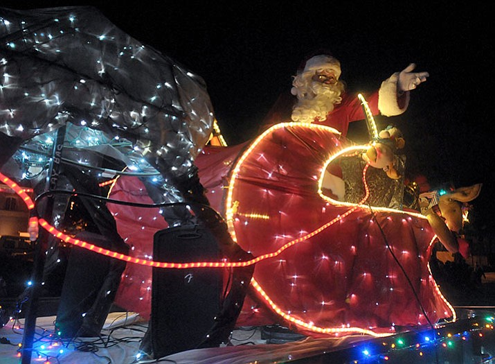 santa claus waves to the crowd in his christmas light covered sleigh during the 2015