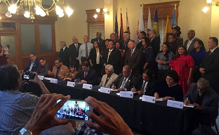 Gov. Doug Ducey, fifth from left sitting, signs the deal with tribal leaders representing 10 tribes.
