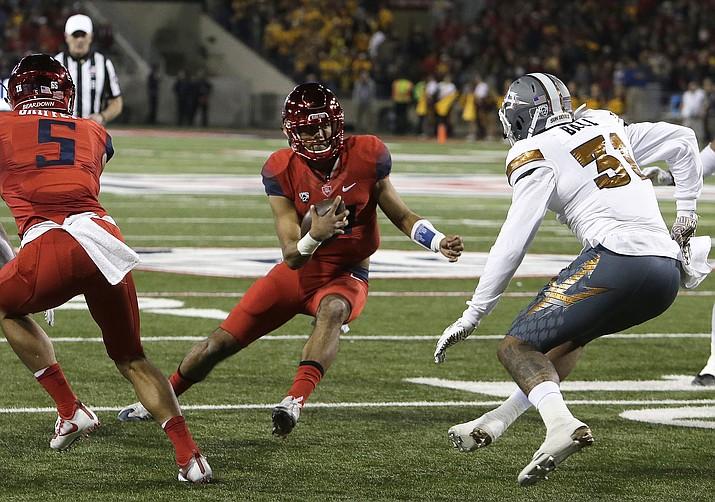 Arizona quarterback Brandon Dawkins (13) runs for a touchdown against Arizona State during the first half of an NCAA college football game, Friday, Nov. 25, 2016, in Tucson, Ariz.
