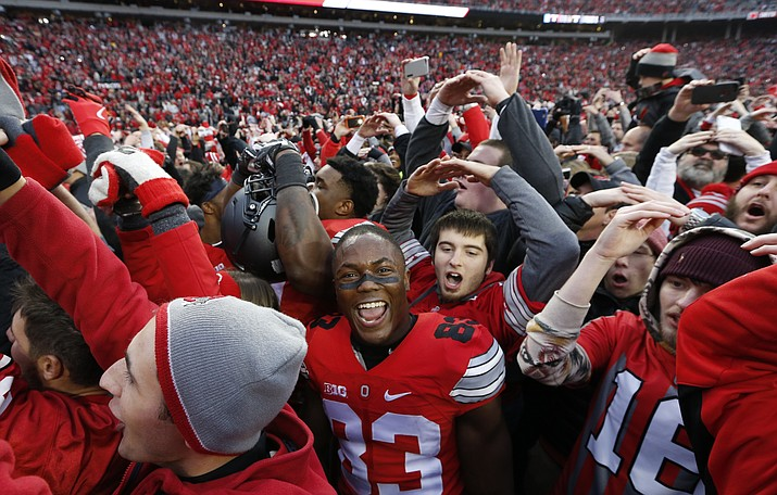 Ohio State players and fans celebrate their win over Michigan on Saturday in Columbus, Ohio. Ohio State beat Michigan 30-27 in double overtime.