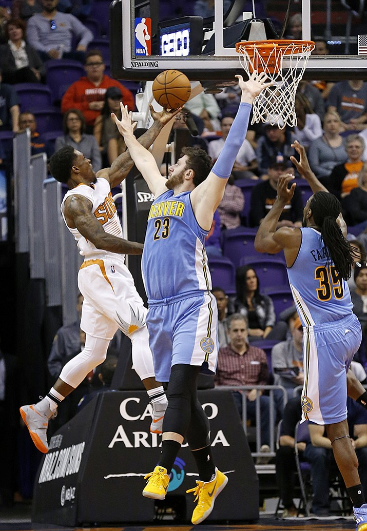 Phoenix Suns guard Eric Bledsoe, left, drives past Denver Nuggets center Jusuf Nurkic (23) and forward Kenneth Faried (35) during the first half of an NBA basketball game Sunday, Nov. 27, in Phoenix.