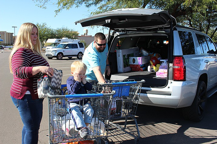 Gentry Nuessle loads a big-screen TV and other merchandise purchased from Walmart on Black Friday. He's accompanied by his wife, Kelly, and son, Logan.