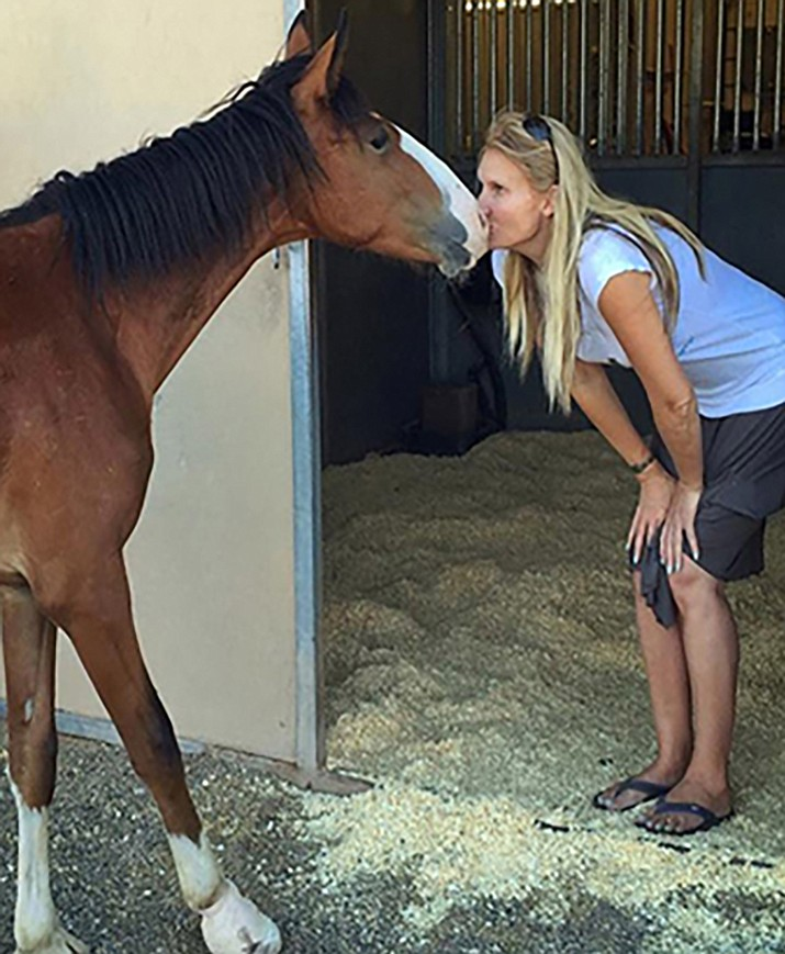 Prescott resident Simone Netherlands, president of the Salt River horse group, kisses the nose of the foal Diamond - one of the rescued foals.