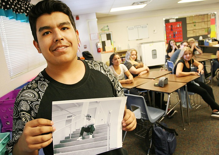 """Cottonwood Middle School eighth grader Steven Ruiz shows the class his self-portrait. """"I wanted half of my face in the photo,"""" said Ruiz. (Photo by Bill Helm)"""