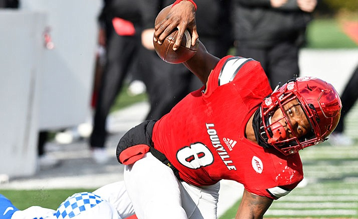 Louisville quarterback Lamar Jackson is brought down by Kentucky's Denzil Ware during the second half of an NCAA college football game, Saturday, Nov. 26, in Louisville, Ky. Kentucky won 41-38.