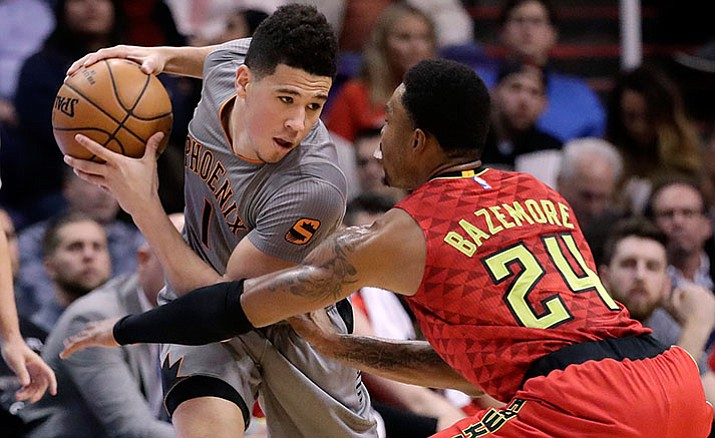 Phoenix Suns guard Devin Booker is defended by Atlanta Hawks forward Kent Bazemore (24) during the first half Wednesday night in Phoenix.