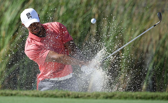 Tiger Woods hits from a bunker onto the sixth green during the Pro-Am at the Hero World Challenge golf tournament Wednesday afternoon in Nassau, Bahamas.
