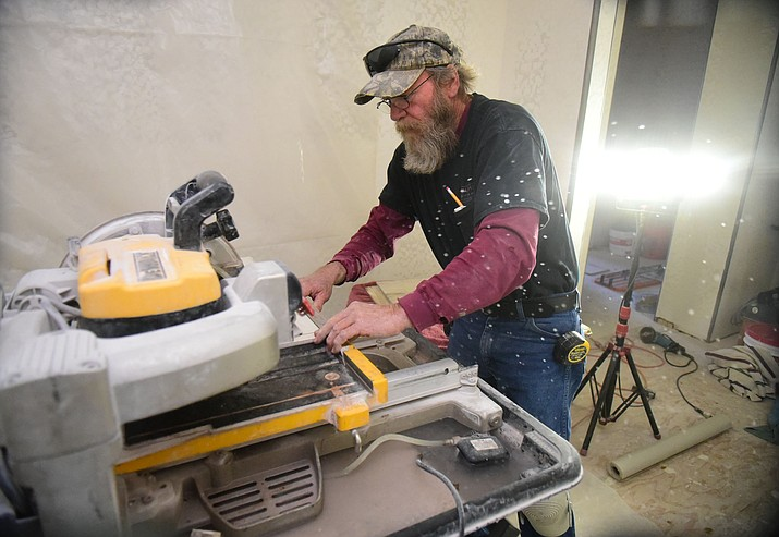 Mile High Tile's Ronnie Llewellyn cuts a piece of tile during an extensive home renovation and garage add-on by Renovations in a home on Sequoia Drive in Prescott Friday, December 2. (Les Stukenberg/The Daily Courier)