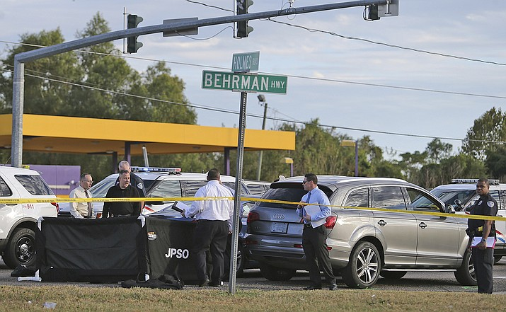 The body of former NFL player Joe McKnight lies between the shooter's vehicle at left and his Audi SUV at right as the Jefferson Parish Sheriff's Office investigates the scene in Terrytown, La., Thursday, Dec. 1.