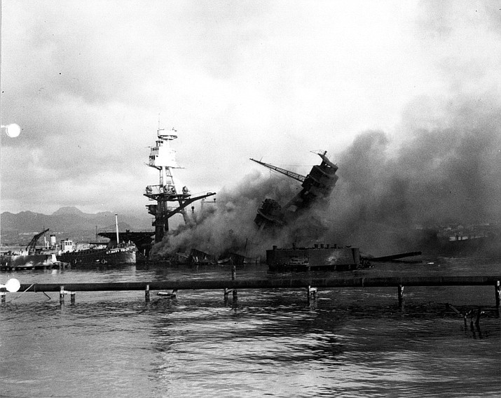 The USS Arizona is ablaze and smoking following the Japanese bombing of Pearl Harbor on Dec. 7, 1941. The ship sank and took the lives of 1,177 servicemen, nearly half the total casualties suffered by the U.S. Pacific Fleet.