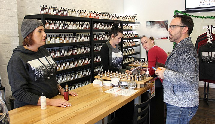 Manager of JVapes Prescott location, Amelia Libby (left), speaks with Rick Levang (right), Wholesale Manager for JVapes, as Levang purchases e-juice.