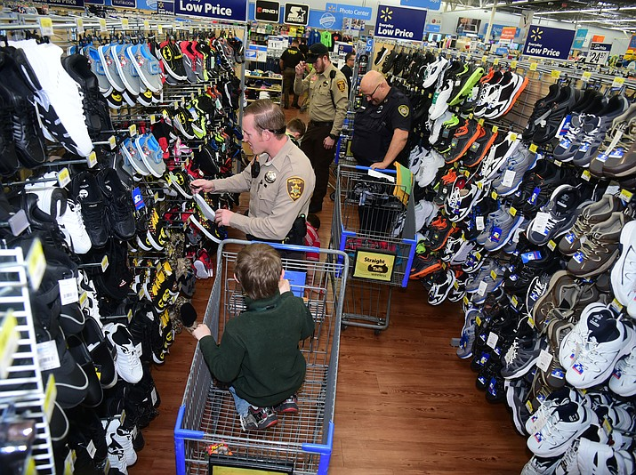Law enforcement officers from 11 area agencies treated 91 children to a $250. shopping spree as part of the 19th Annual Shop with a Cop at the Prescott Valley Walmart Saturday, December 10.  (Les Stukenberg/The Daily Courier)