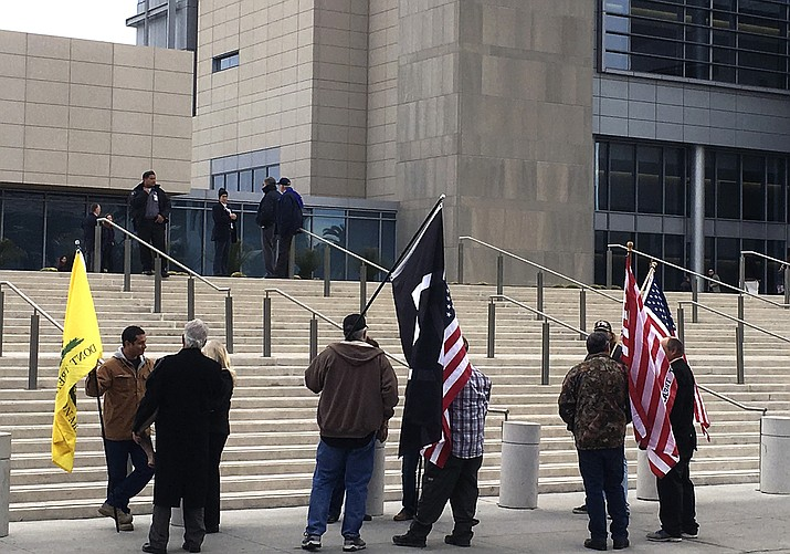 A small group of protesters gather Friday, Dec. 9, outside the U.S. District Court building in Las Vegas where Nevada rancher Cliven Bundy and 16 other defendants had a hearing before a federal magistrate judge scheduling their trials on charges they conspired to take up weapons against federal agents in an armed standoff in April 2014.