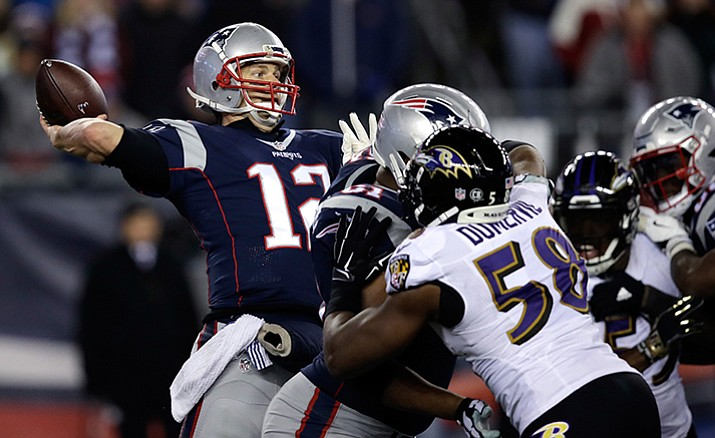 Patriots quarterback Tom Brady throws a touchdown pass under pressure from Baltimore Ravens linebacker Elvis Dumervil during their NFL football game, Monday, Dec. 12, in Foxborough.