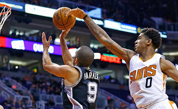 Phoenix Suns forward Marquese Chriss (0) blocks the shot of San Antonio Spurs guard Tony Parker (9) during the first half of an NBA basketball game Thursday, Dec. 15, in Phoenix.