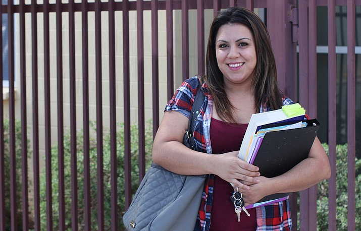 Cottonwood's Zahide Betancourt, 28, holds her textbooks in front of Wilson Community Center in Phoenix, where she takes a GED prep course. (Photo by Cassie Ronda/PIN Bureau)