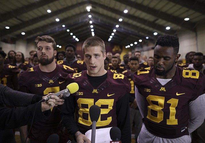 Members of the University of Minnesota football team stand with Drew Wolitarsky, center, as he read a statement Thursday night, Dec. 15, that players would not be participating in any football activities until a resolution could be found regarding the suspension of 10 of their teammates.