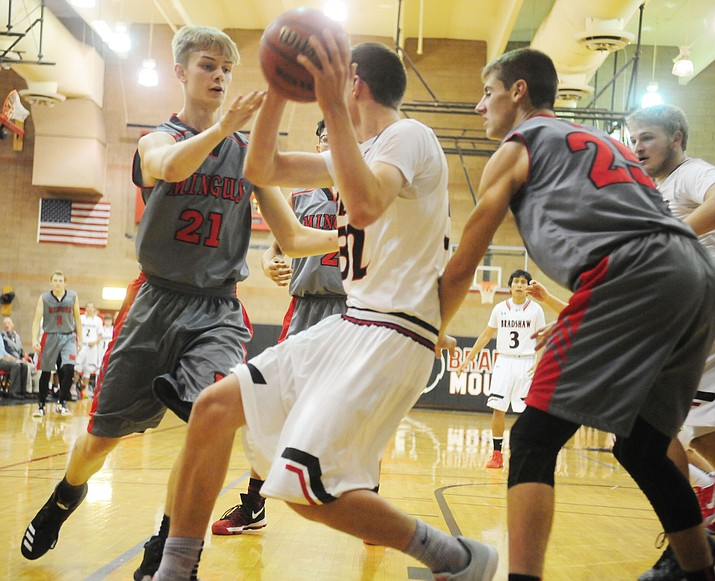 Two Mingus defenders swarm Bradshaw Mountain High School for the ball during Friday's 62-61 overtime win for Mingus on the road. (Photo by Les Stukenberg)