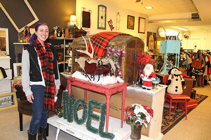 Leah Burkhart stands next to an elaborate Christmas display at Gracie's Vintage and Thrift store in downtown Kingman.