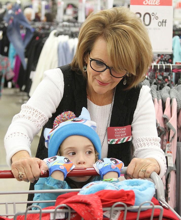 Volunteer Renee Hill helps Zoey Frigga, 6, choose an outfit.