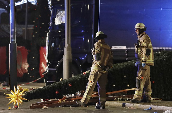 Firefighters look at a toppled Christmas tree after a truck ran into a crowded Christmas market and killed several people in Berlin, Germany, Monday, Dec. 19.