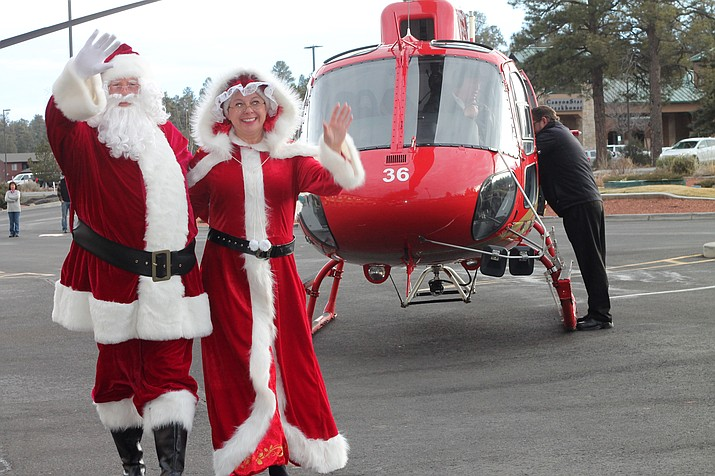 Santa and Mrs. Claus arrive via helicopter at the Best Western Premier Grand Canyon Squire Inn.