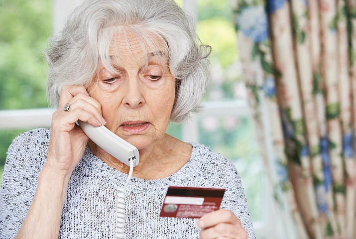A woman gives her credit card information over the phone.