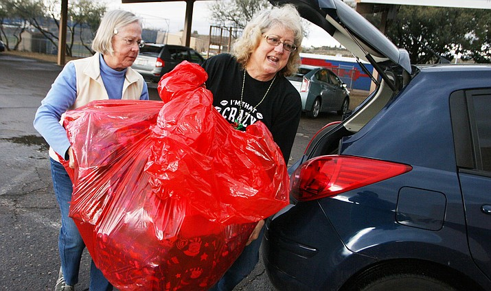 Friday, Camp Verde resident Liz Stark, left, helps Irene Peoble bring donations from Bashas' for the Camp Verde Kiwanis' annual Adopt-a-Family program. Close to 130 adopted families picked up Christmas presents on Dec. 17. (VVN/Bill Helm)