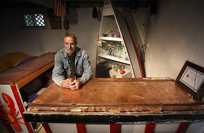 In this Nov. 2, 2016 photo, Glenn Adams poses behind a bar he made from parts of a sunken 18-foot boat and copper that once covered the dome at the Maine State House, at his camp in Richmond, Maine. The boat was cut into three pieces, two for the bars, and one for shelving in the background. (AP Photo/Robert F. Bukaty)