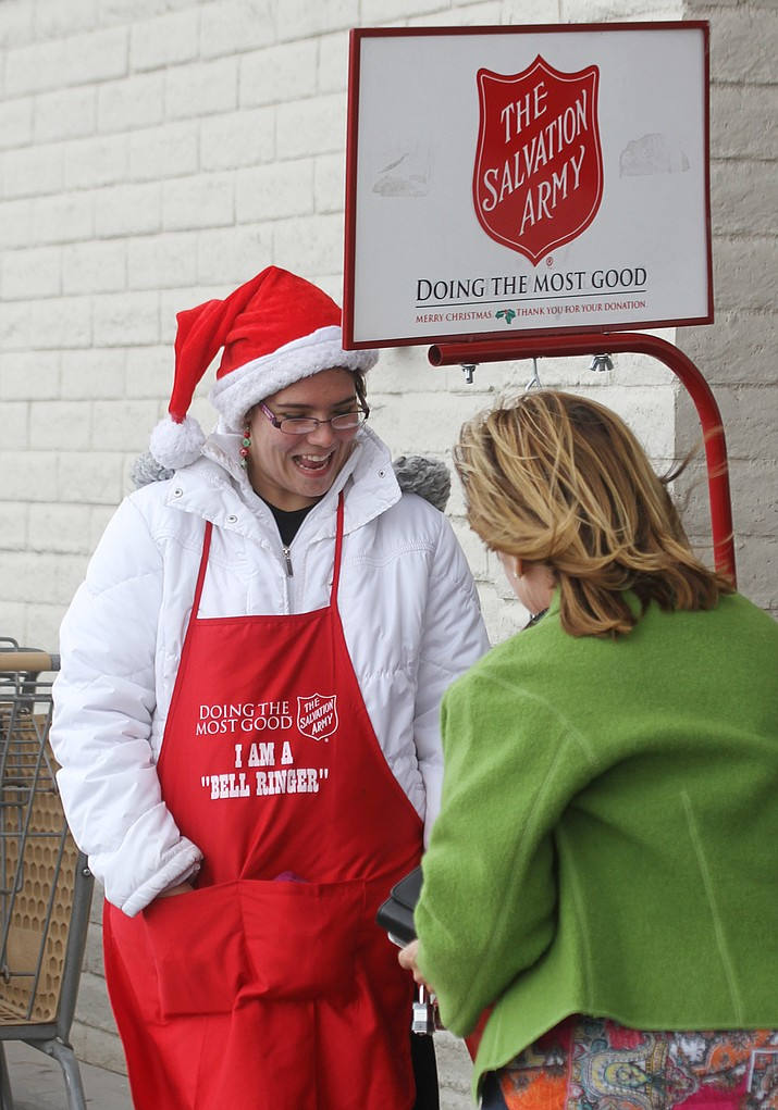 "Sara Leblanc is a volunteer for the Salvation Army. Here she stands in front of Safeway Friday afternoon as Brenda Curwick donates some money. Leblanc enjoys volunteering for the Salvation Army as a bell ringer, stating, ""It's a good thing to do. I meet all kinds of people; share the spirit of the holiday. It's a time of giving, not receiving, a time for Christmas miracles. The Salvation Army is a great company… I love it. I've seen friends, teachers, neighbors I haven't seen in years (while doing this job). They tell me about the Salvation Army and how they wouldn't be where they are today without them. (The Salvation Army) has helped a lot of people."""