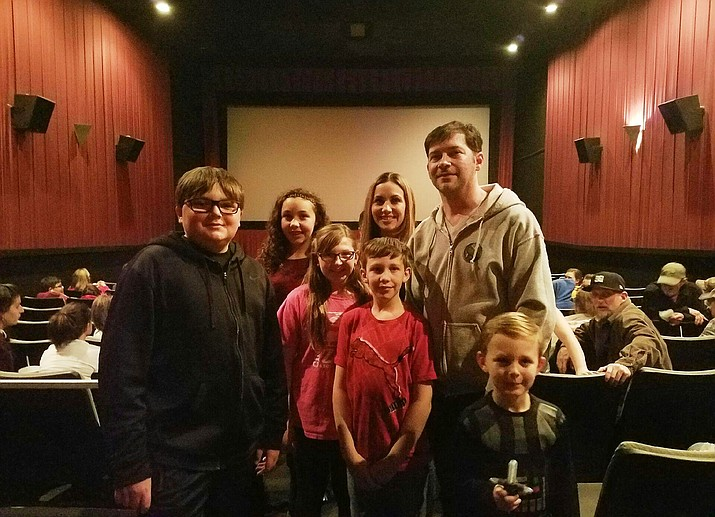 Preston (top right) stands with Layne Carr-Cullison, 5 (front right), who was there in costume, and family and friends just before the movie started.