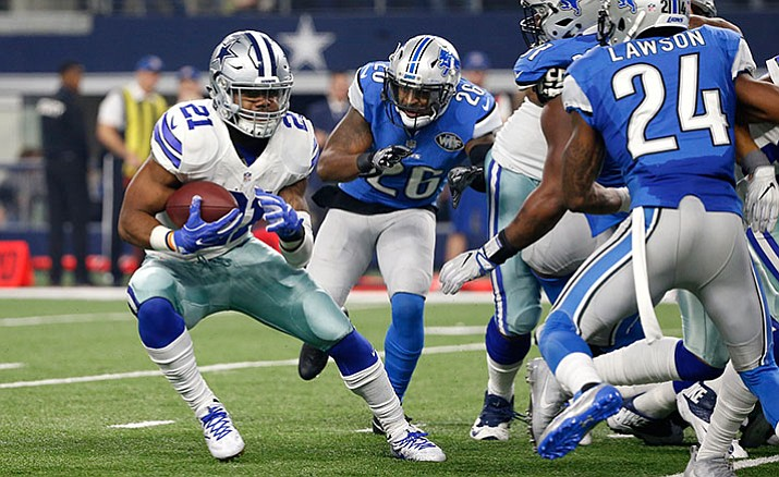 Dallas Cowboys' Ezekiel Elliott (21) evades pressure from Detroit Lions' Don Carey (26) and Nevin Lawson (24) as Elliott sprints to the end zone for a touchdown in the second half of an NFL football game, Monday, Dec. 26, in Arlington, Texas.