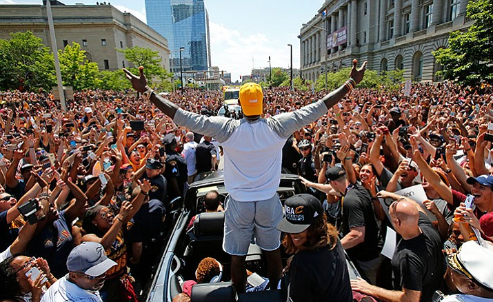 Cleveland Cavaliers' LeBron James, center, stands in the back of a Rolls Royce as it makes its way through the crowd lining the parade route June 22 in downtown Cleveland, celebrating the basketball team's NBA championship. On Tuesday, Dec. 27, James, who ended 52 years of sports heartache by bringing Cleveland a championship, was chosen as The Associated Press 2016 Male Athlete of the Year.