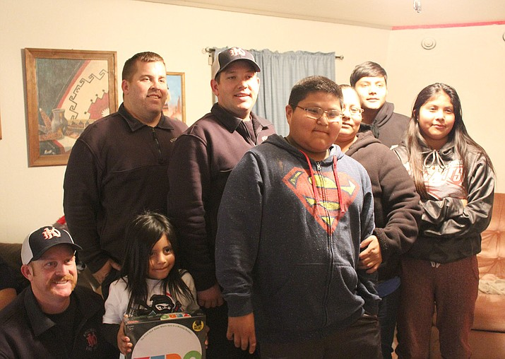 Members of the Kingman Fire Department and the Watahomigie family share a Christmas evening with the Black family.