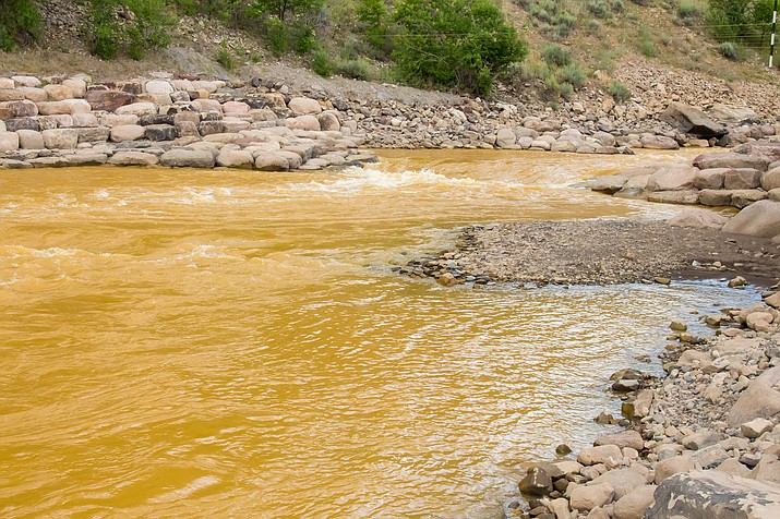 Orange hued river water due to an accidental spill of toxic mine waste by the EPA. Photo/Adobe stock image