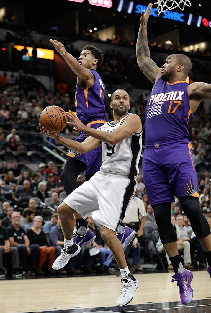 San Antonio Spurs guard Tony Parker (9) drives between Phoenix Suns defenders P.J. Tucker (17) and Suns forward Marquese Chriss (0) during the first half of an NBA basketball game, Wednesday, Dec. 28, in San Antonio.