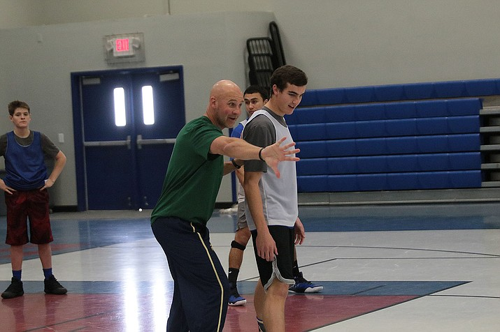 Kingman Academy principal Jeff Martin demonstrates how the Tigers should be playing defense with his son, Cade Martin, during Wednesday's practice.