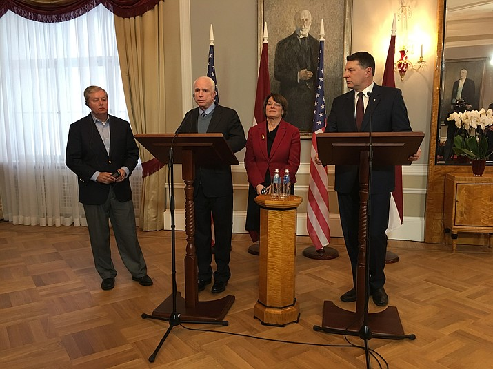 Latvian President Raimonds Vejonis, right, looks at US Sen. John McCain centre left, during a press conference, Wednesday, Dec. 28, 2016 in Riga, Latvia, while Lindsey Graham, R-SC., and Amy Klobuchar, D-Minn., stand in the background. Russia can expect hard-hitting sanctions from United States lawmakers if an investigation proves that Moscow interfered in the presidential election, a U.S. senator said Wednesday during a visit to Latvia.