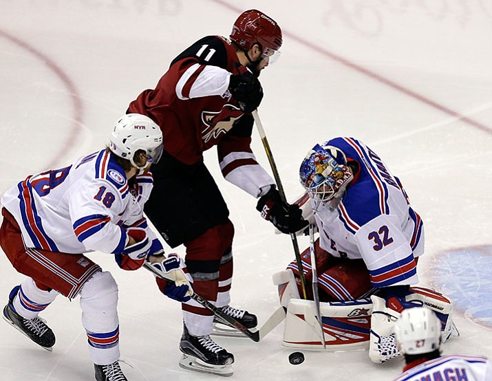 New York Rangers goalie Antti Raanta (32) makes the save on Arizona Coyotes center Martin Hanzal (11) while Marc Staal (18) defends during the third period of an NHL hockey game, Thursday, Dec. 29, in Glendale.