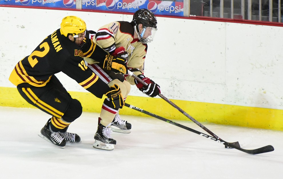 ASU's Dylan Hollman battles with Brown's Max Willman as the ASU Sun Devils take on the Brown Bears from Rhode Island in the Desert Hockey Classic at the Prescott Valley Event Center Friday, December 30. (Les Stukenberg/The Daily Courier)